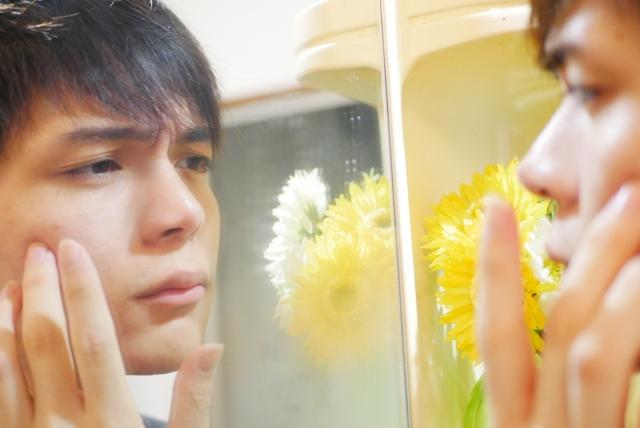 鏡でニキビを気にする男性